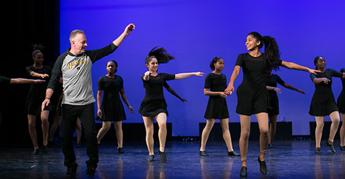 Dr. Martirano in a dance class on stage with students.